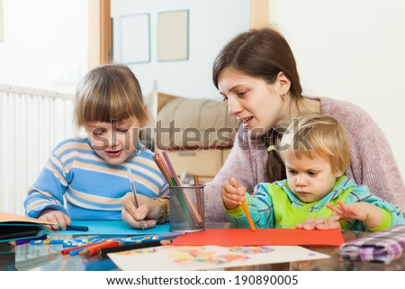 Woman and  children together drawing with pencils in home interior - stock photo
