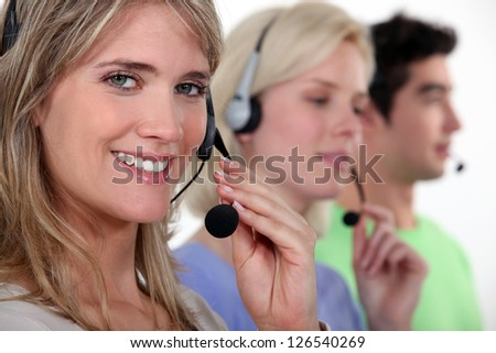 Woman and colleagues wearing headsets - stock photo