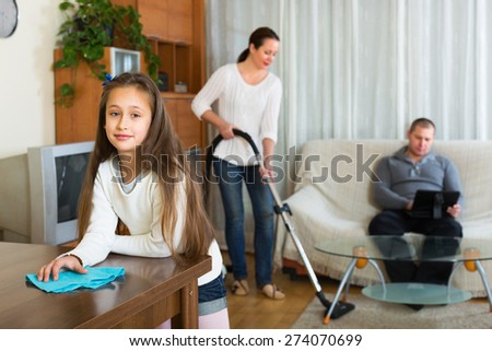 Woman and cute little girl doing general cleaning, man having rest - stock photo