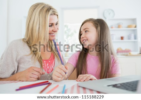 Woman and daughter smiling at each other at the kitchen and drawing - stock photo