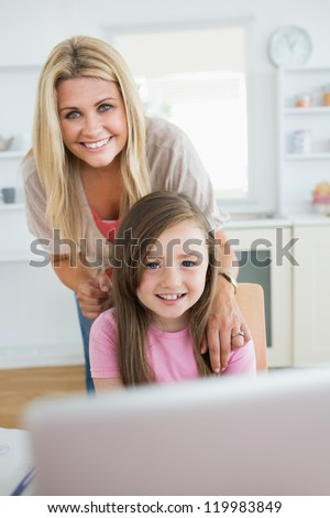 Woman and daughter smiling at the laptop in the kitchen - stock photo