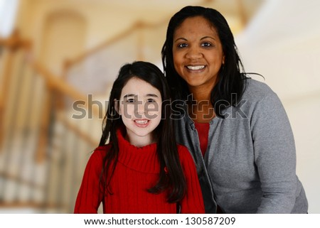 Woman and daughter standing inside their home - stock photo