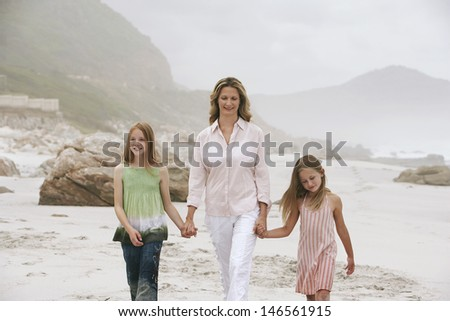 Woman and daughters holding hands while walking on beach