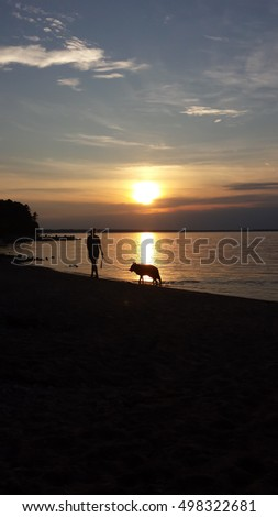 Woman and dog at sunset.