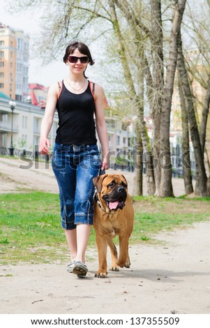 woman and dog bullmastiff walking to the park. girl holding a puppy on a leash