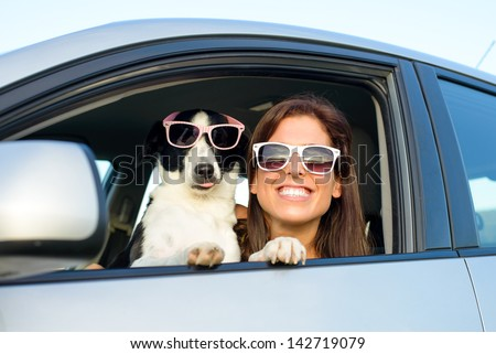 Woman and dog in car on summer travel. Funny dog with sunglasses traveling. Vacation with pet concept. - stock photo