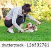 woman and dog plays with a stick on a lawn - stock photo