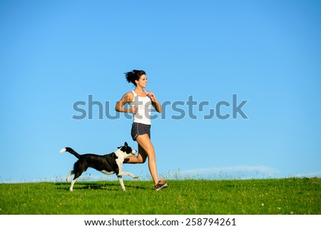 Woman and dog running and exercising outdoor at grass field on summer or spring. Happy female athlete training with her pet. - stock photo