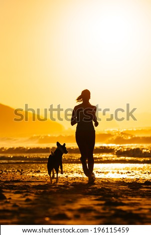 Woman and dog running on beautiful summer sunset or sunrise at beach. Female athlete with her pet training together. - stock photo