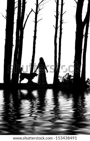 woman and dog silhouettes between trees with water reflections - stock photo