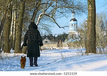 Woman and dog walk to St. Nikolai's cathedral across winter park. Shot in Poltavska region, Ukraine. - stock photo