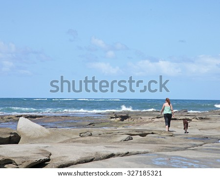 Woman and dog walking on rocks at sea side - stock photo