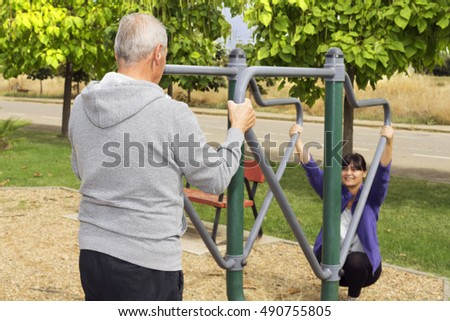 woman and elderly man exercising with  fitness equipment in public outdoor gym , selective focus on man