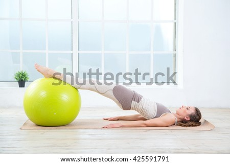 Woman and fitness ball. Young woman doing exercises with fit ball at gym. Woman is doing fitness at home on room floor near the window.