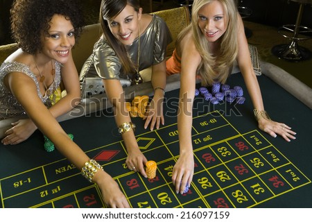 Woman and friends placing gambling chips on roulette table, portrait, elevated view - stock photo
