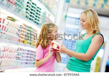 woman and girl choosing produces in dairy shopping mall - stock photo