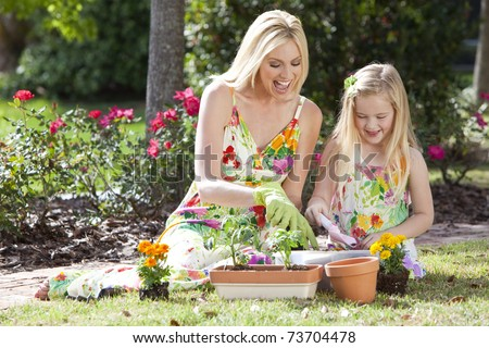 Woman and girl, mother and daughter, gardening together planting flowers and tomato plants in the garden - stock photo