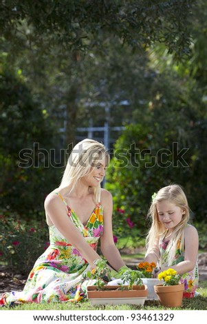 Woman and girl, mother and daughter, gardening together planting flowers and tomato plants in the garden