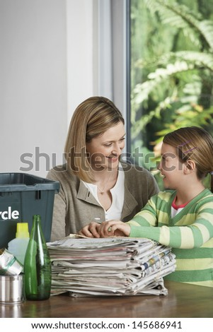 Woman and girl preparing waste paper for recycling at home - stock photo
