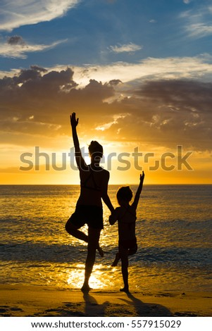 woman and girl silhouette practicing balancing yoga the pose together during ocean sunset with bright orange sky and water reflections