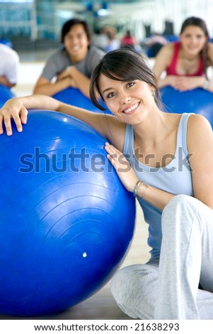 woman and group of people doing pilates in a gym - stock photo