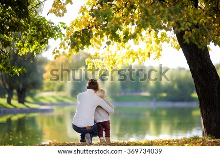 Woman and her adorable toddler son in sunny park  - stock photo