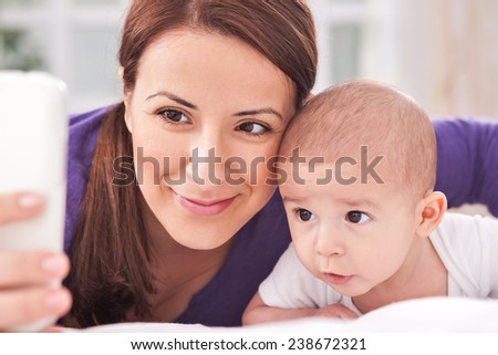 Woman and her baby taking selfie at home - stock photo