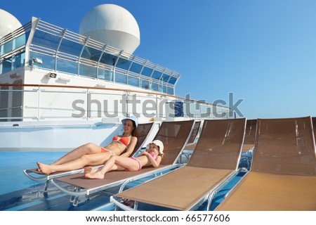 woman and her daughter both wearing swimsuit on chaise lounge - stock photo