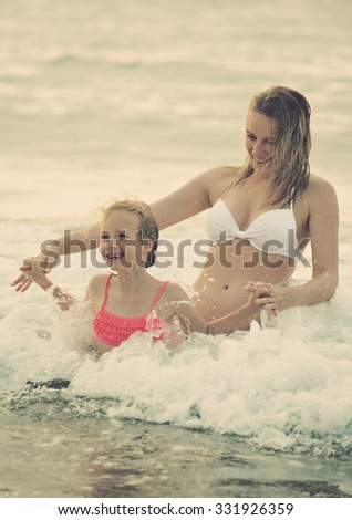 Woman and her daughter having fun in the sea. Vintage effect.