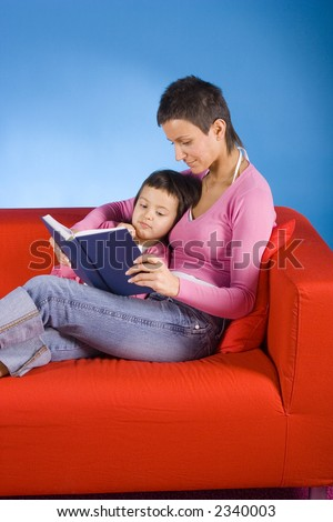 woman and her dauther sitting on the red sofa and reading the book - stock photo