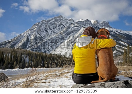 woman and her dog admiring the view sitting on a rock facing the mountains in the background - stock photo