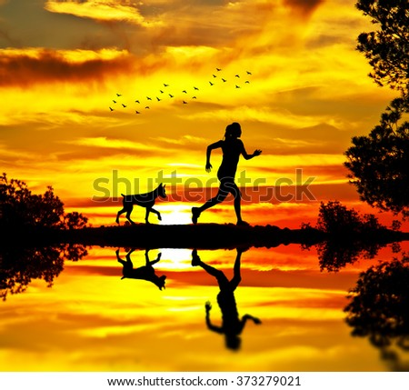 woman and her dog running across field - stock photo