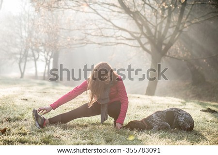 Woman and her dog stretching outdoor. Fitness girl and her pet working out together. - stock photo