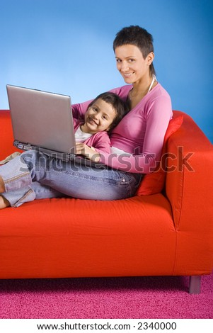woman and her doughter sitting on the sofa, playing with computer - stock photo