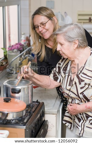 Woman and her elderly mother cooking a meal together - stock photo