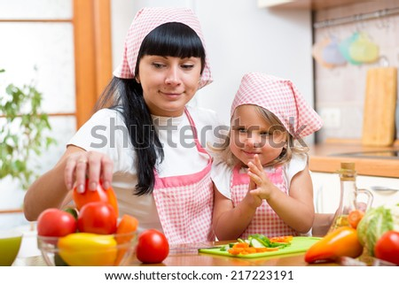 woman and her kid daughter are cooking  at kitchen