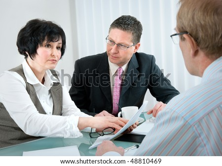 woman and her lawyer in conversation with husband during divorce process - stock photo