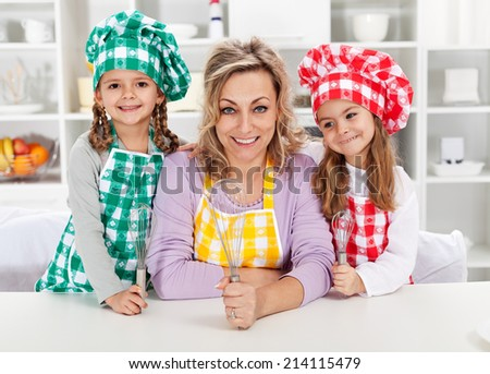 Woman and her little helper chefs in the kitchen, ready for some cooking or baking - stock photo