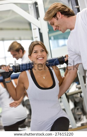 woman and her trainer doing exercise at the gym