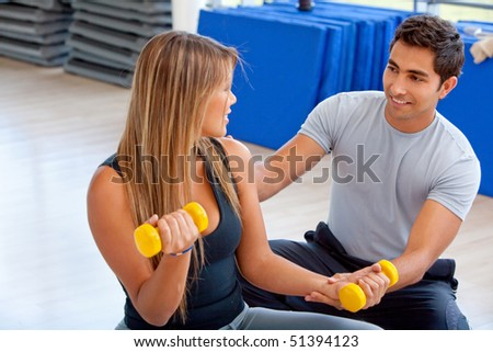 Woman and her trainer exercising at the gym - stock photo