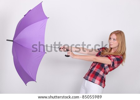 Woman and her umbrella being swept away by the wind