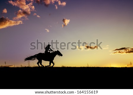 Woman and horse running at dusk with colorful sunset - stock photo
