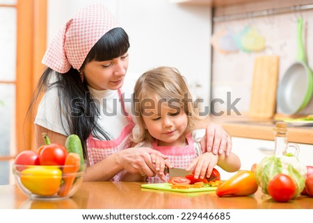 woman and kid daughter preparing healthy food - stock photo