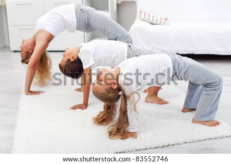 Kids doing bridge stretch gymnastic exercises at home stock photo