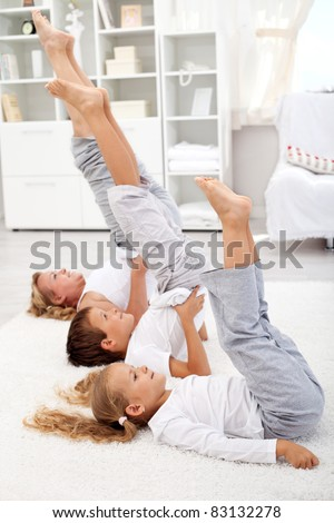Woman and kids doing gymnastic exercises at home - closeup, focus on the first kid