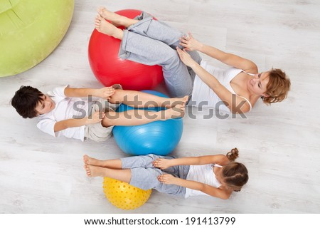 Woman and kids exercising together at home - with large gymnastic walls, top view - stock photo