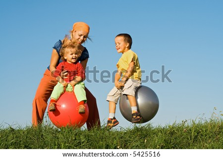 Woman and kids jumping on large balls in the grass under clear blue sky - stock photo