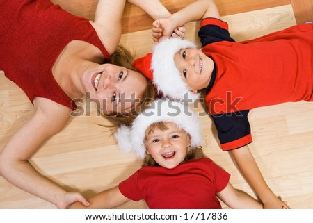 Woman and kids laying on the floor in christmas time smiling - stock photo