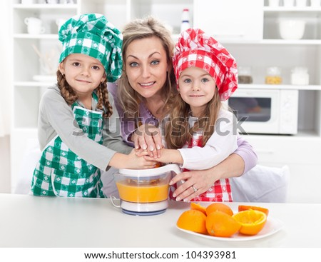 Woman and kids making fresh fruit juice - dressed as chefs in the kitchen - stock photo