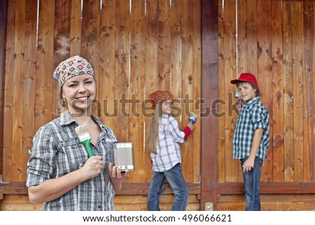 Woman and kids painting the wood shed - in front of the wooden wall